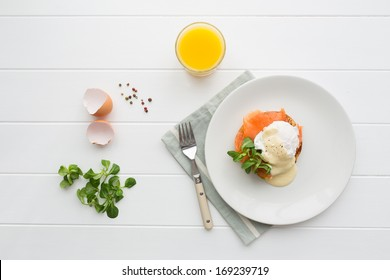 Top view of healthy breakfast with poached eggs royale (benedict), fresh orange juice and green salad