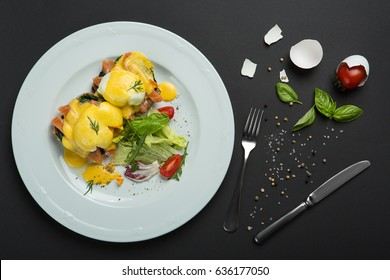 Top view of healthy breakfast with poached eggs royale, benedict with salmon and green salad on black