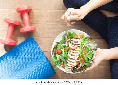 Top view healthy girl eating chicken salad. Dumbbells and yoga mat on the floor