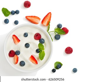 Top view of healthy Greek yogurt in a bowl with fresh berries isolated on white background.