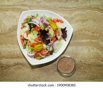 Top view of a healthy green salad with fresh vegetables and salad dressing on the side.