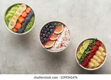 top view of healthy organic smoothie bowls with fruits on grey background