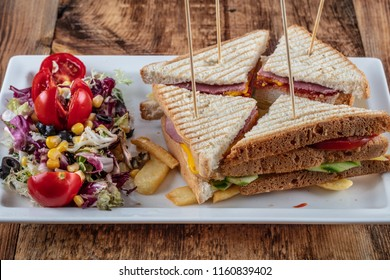 Top view of Healthy Sandwich toast with lettuce, ham, cheese and tomato on a wooden background.