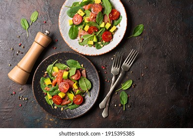 Top view of healthy and tasty food. Salad with fresh baby spinach leaves, cherry tomatoes, sliced avocado and salty red salmon fish on dark concrete background