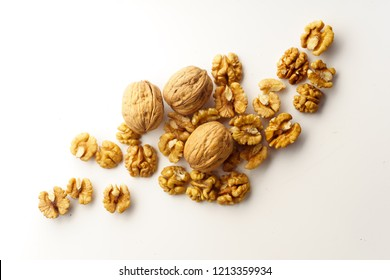 Top view of a heap of raw walnuts with a nutshell on white background isolated with copy space
