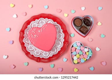 Top view heart cake on red decorative plate with white doily box of candy hearts and chocolates on pink background.