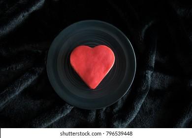 Real duck vertebrae in a heart shaped frame on red velvet