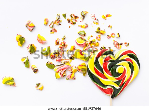 top view of heart and roughly broken lollipops on white background. Sweet sucker, lollipop, candy, minimal concept above decoration, food background