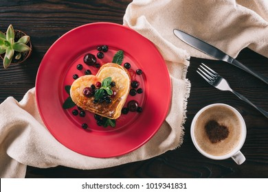 top view of heart shaped pancake with berries and mint on wooden table, valentines day concept
