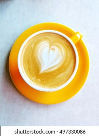 Top view of a heart shaped in a yellow cup of latte, cappuccino coffee. Cafe art design with milk, cofee, round ceramic glass and plate for coffe lovers - aka latte art.