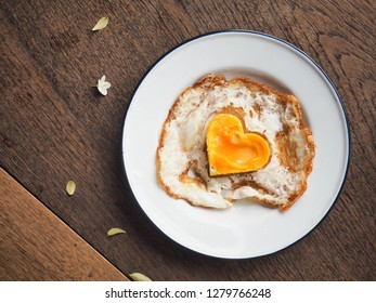 Top view of heart yolk sunny side up on plate on wood table with small leaf and flower decoration. Sweet Breakfast for special day like Valentine's day, Anniversary, Date or birthday