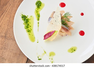 Top view of a herring with potatoes served on a white plate
