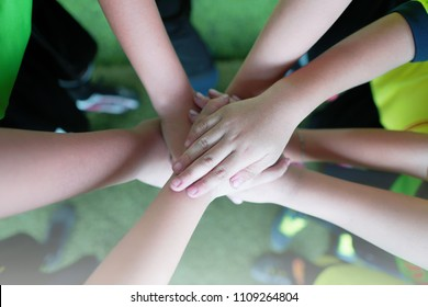 Top view of high five kids hand gesture in junior football team.Boy standing in circle with stack of hands togethershowing unity.Symbol of celebration or greeting,Success and teamwork Concept.