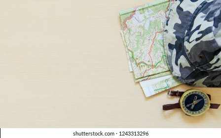Top view of hiking hat, map and compas on the corner of the desk. Flat lay. Copy space. Minimalism