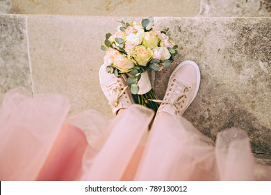 Top view of hipster bride's legs in rose sneakers with a bouquet between them.