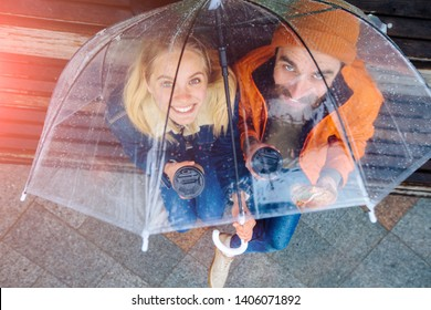 Top view of hipster woman and beard man sitting under umbrella on bench drinking coffee takeaway, looking at camera in rainy cold spring day. Weather forecast concept.