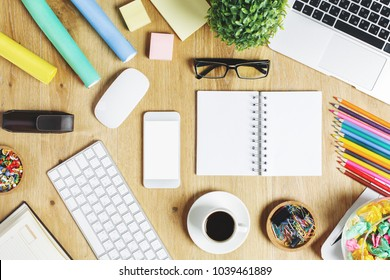 Top view of hipster wooden office workspace with empty notepad, electronic device, other supplies and coffee cup. Lifestyle, project and occupation concept. Mock up