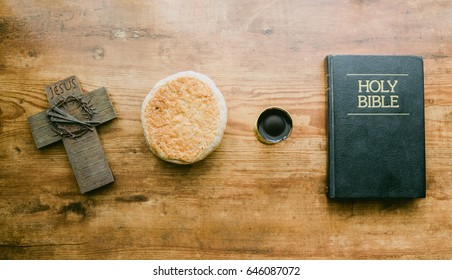 Top view of holy communion on wooden table on church.Taking Communion.Cup of glass with red wine, bread and Holy Bible and Cross on wooden table.