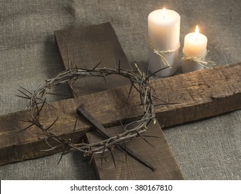Top view of a holy cross, crown of thorns and candles on a burlap background.
