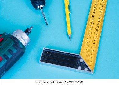 Top view of home construction tools and equipment - cordless drill, pencil, drill bit and 12 inches 30cm Construction Carpenter Ruler L Shape Angle Square Rule on a aqua blue color background.