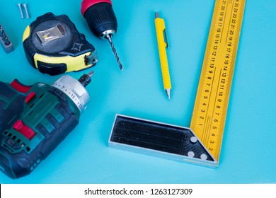 Top view of home construction tools - cordless drill, pencil, drill bit, metal roll ruler and 12 inches 30cm Construction Carpenter L Shape Angle Square Rule on a aqua blue color background.