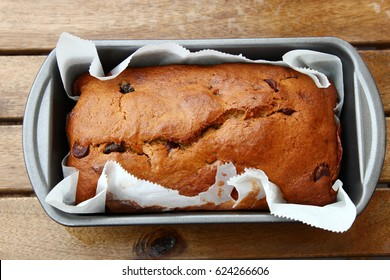 Top view of home made vegan Banana bread with chocolate chips in a loaf pan on a wooden table.