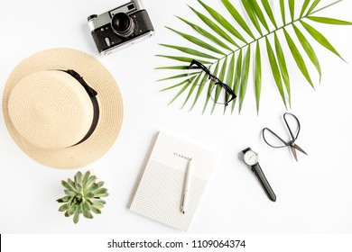 Top view home office desk. Workspace with straw hat, glasses, retro camera, notepad and tropical palm leaf on white background. Flat lay, top view.