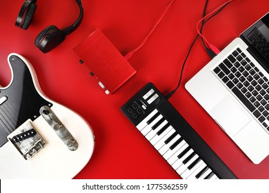 Top view of home recording studio equipment, electric guitar, MIDI keyboard, audio interface and headphone on red background.
