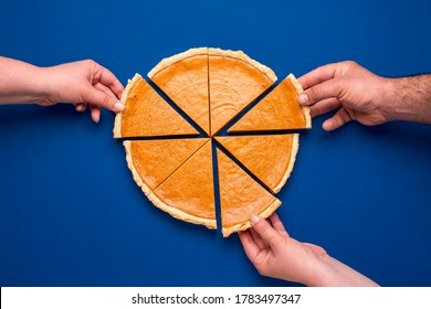 Top view with a home-baked pumpkin pie isolated on a blue colored background. Three people grabbing with their hand's slices of pumpkin cake - Shutterstock ID 1783497347