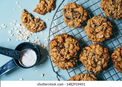 Top view of homemade cranberry and oats cookies, with flour and oats on the side, sitting on a cooling rack on light background,