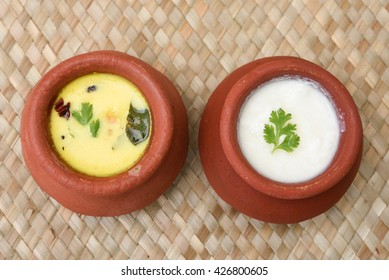 Top view of homemade curd and spiced butter milk or butter milk or moru curry in clay pot made from cow milk in Kerala, India. Food in Indian clay / mud pots.