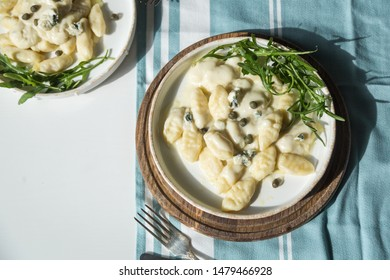 Top view of homemade gnocchi with creamy gorgonzola sauce, capers and arugula in white plate on wooden board.