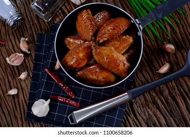 Top view of homemade grilled chicken wings in frying pan. Decorated with ingredients on wooden table with copy space. Concept about food preparation in the kitchen.
