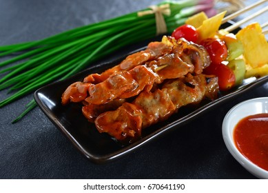 Top view of homemade grilled pork barbecue stick and vegetables on the black plate with spicy sauce. Black stone background. Rustic style for designed work. BBQ Foods. Dark Tone. Colourful Vegetables.