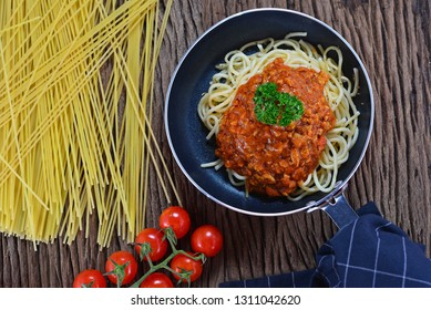 Top view of homemade spaghetti bolognese in frying pan. Decorated with cherry tomatoes, ingredients on background. Concept about food preparation in the kitchen.Homemade Cooking with copy spcae