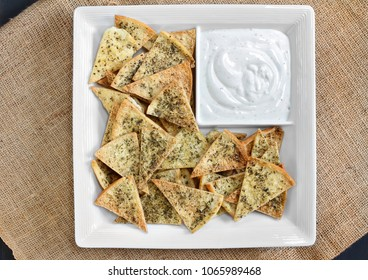Top view of homemade spicy pita chips with dip.  Chips and dip are in a white chip dish.