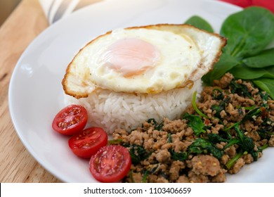 Top view of Homemade Stir fried minced pork with basil served with steamed jasmin rice and fired egg, Thai famous spicy food, Thai name is Pad kra pao Kai dow