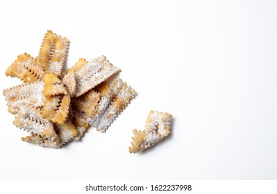 Top view of homemade traditional carnival sweets: chiacchiere on white background. Copy space.