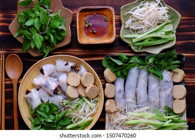 Top view homemade Vietnamese vegan rolled steamed rice pancake or banh cuon in two plate with herb and sauce on wooden background