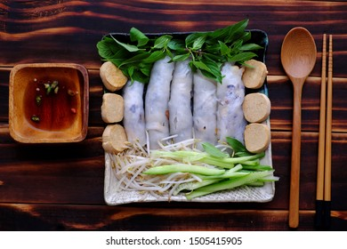 Top view homemade Vietnamese vegetarian rolled steamed rice pancake or banh cuon in plate and sauce on wooden background