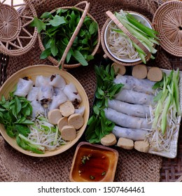 Top view homemade Vietnamese vegetarian rolled steamed rice pancake or banh cuon in two plate with basket of herb and sauce on burlap background