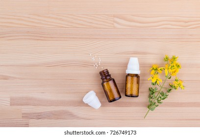 Top view of a homeopathic medicine with blooming St. John's wort on a wooden background with copy space