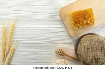 Top view of Honey comb and glass honey jar on wooden white background