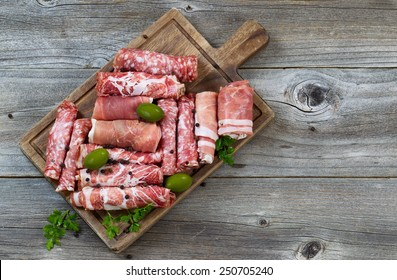 Top view horizontal image of various meats on serving board with ham, pork, beef, parsley, and olives on rustic wood.