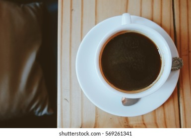 Top view of hot black coffee on the wooden table
