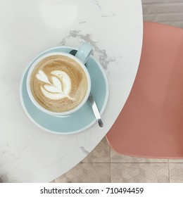 Top view of hot cappuccino with beautiful latte art on the round marble table and pastel color theme.