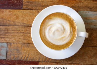 Top view of hot coffee cappuccino cup with milk foam on wood table background