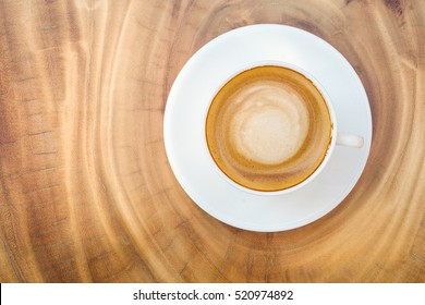Top view of hot coffee cappuccino cup with milk foam on wood table background.