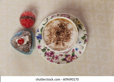 Top view of hot coffee cappuccino cup , with chocolate muffin and sweet bakery. Breakfast time in a italian bed and breakfast