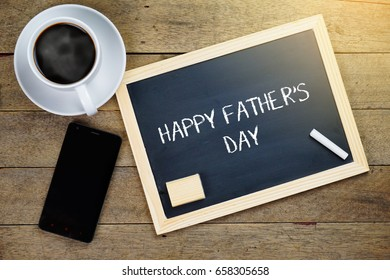 Top view of hot coffee, mobile phone and chalkboard written with HAPPY FATHER'S DAY on wooden background.